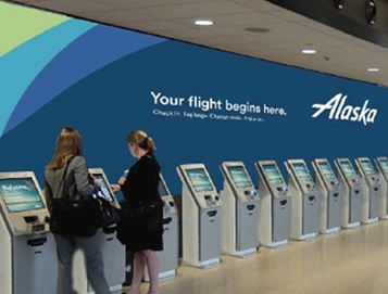 Two women standing at an Alaska Airlines kiosk